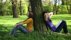 Anxious students sit beside tree